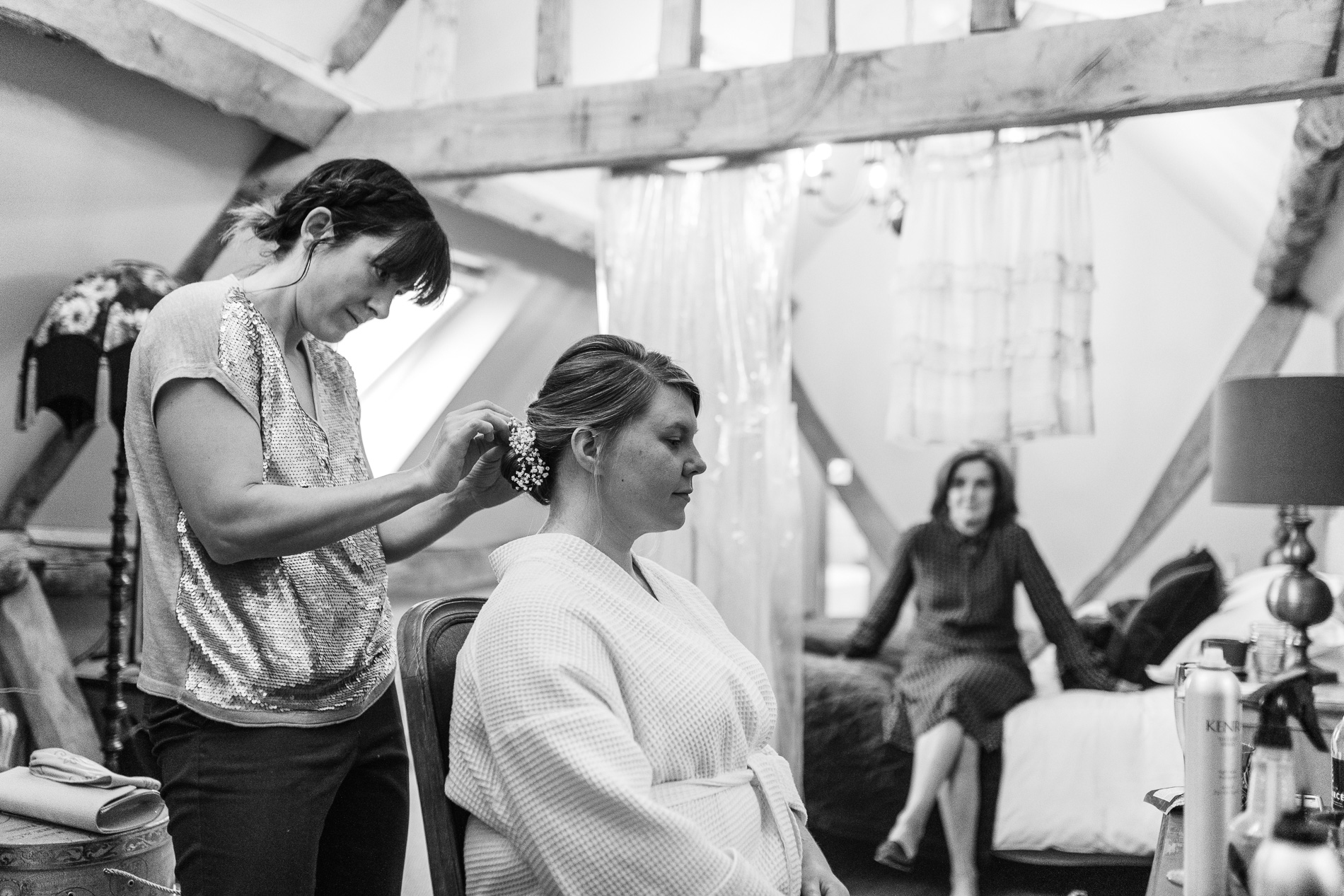 A bride gets her hair done on her wedding morning