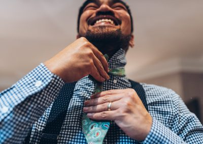 Close up of groom putting his tie on