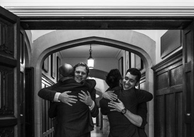 The grooms hugging guests