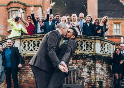 The grooms kissing in front of their guests