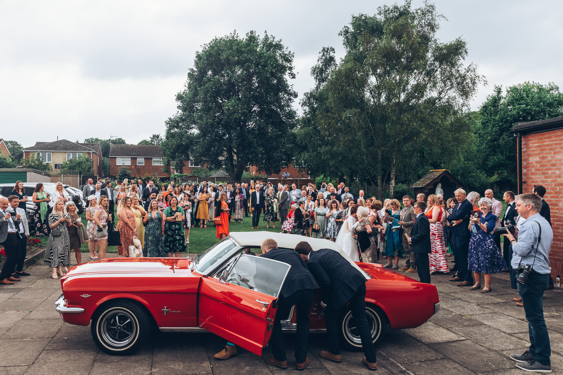 Bride and groom getting into wedding car