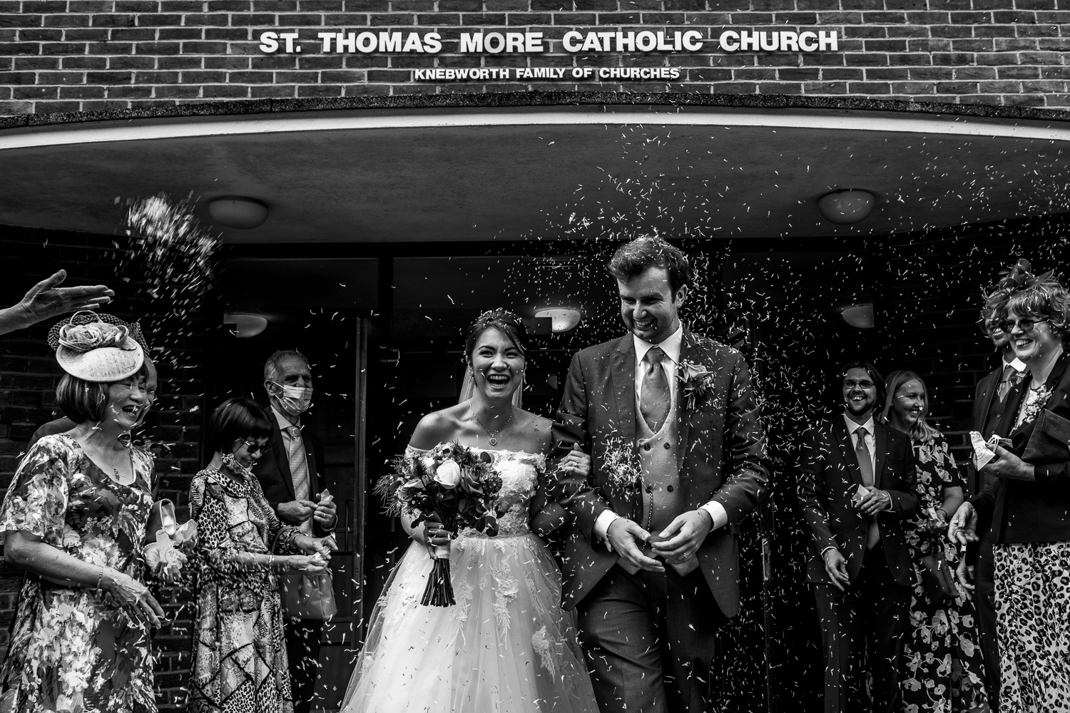 Bride and groom leaving the church while guests throw confetti